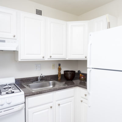 Kitchen with white cabinets inside an apartment at the Enclave