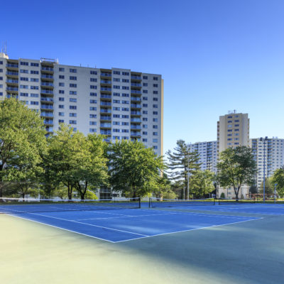 A blue tennis court surrounded by high rise apartments in Silver Spring, MD