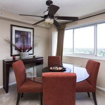 Red chairs surround a table in an Enclave Apartment dining room