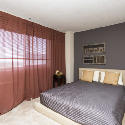 Apartment bedroom with red curtains at the Enclave