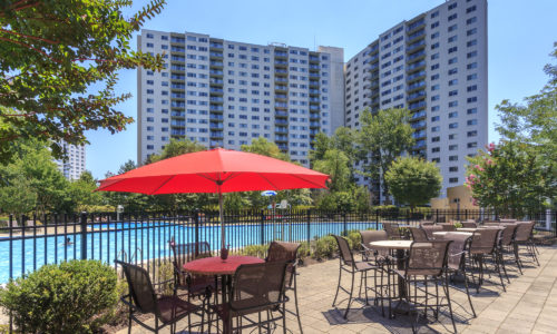 Pool with tables and chairs at the Enclave Apartments in MD